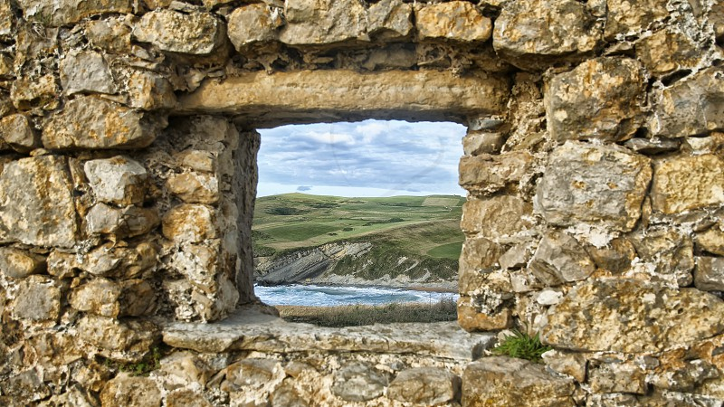 View of the sea and rocks through a window  photo