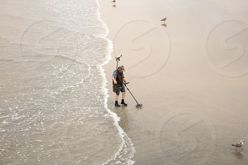 A man uses a metal detector on a beach. photo