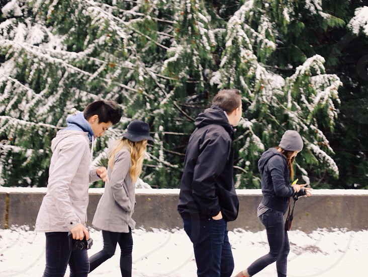 two men and two women walking on the snow photo