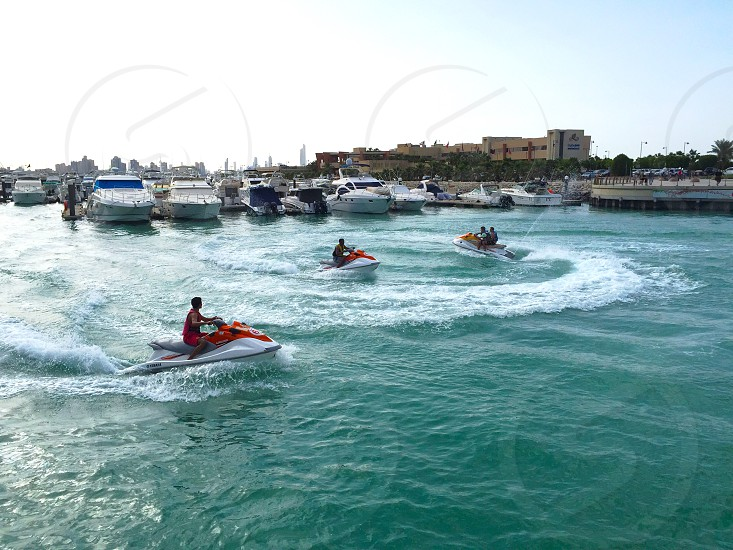 people in jet skis in water under white sky photo