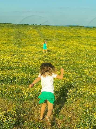 A field of flowers and running girls. photo