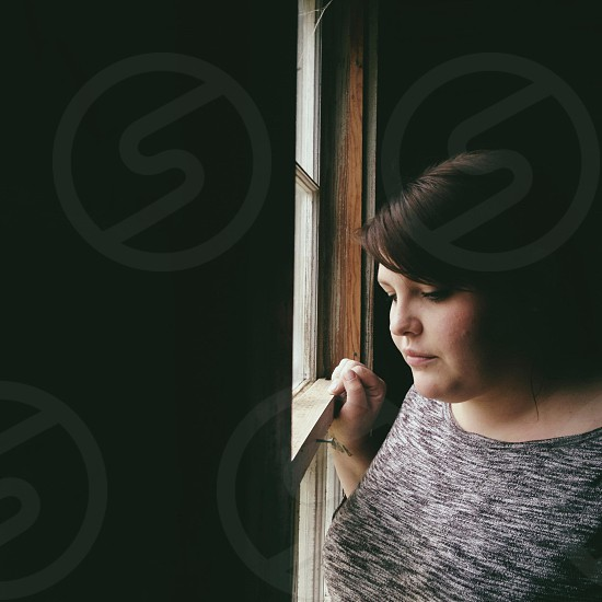 woman with brown hair looking out window in black and gray space dye shirt photo