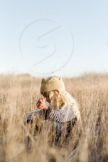vertical child girl crown knit crown sitting field tall grass shallow depth of field nature quiet peaceful gold golden light photo