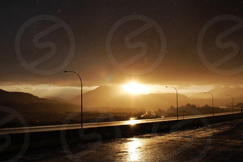 Sunset rain storm golden hour dark sky highway street lights mountain silhouette photo