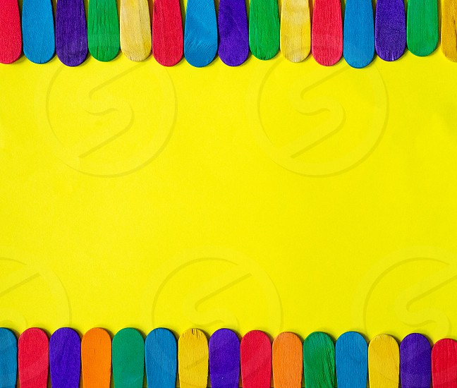 colorful wood ice-cream stick on yellow background. Copy space in middle area. photo