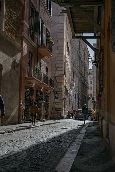 A silent narrow side street with dramatic sunlight paving and two unidentified people walking  photo
