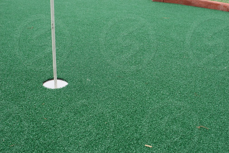 Mini golf hole closeup with astroturf. Portion of flag coming out of hole. photo