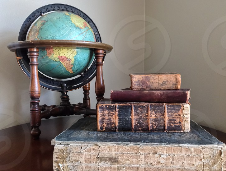 brown hardbound books beside table globe on brown wooden table photo