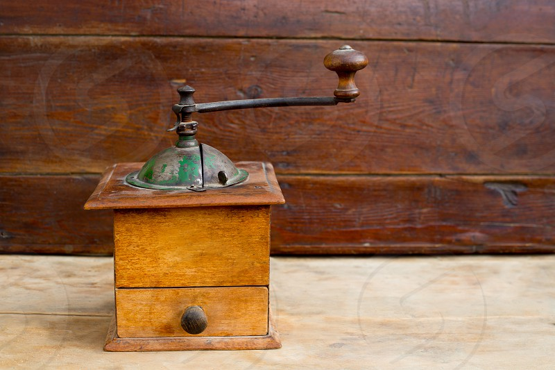 retro old coffee grinder with vintage wooden background photo