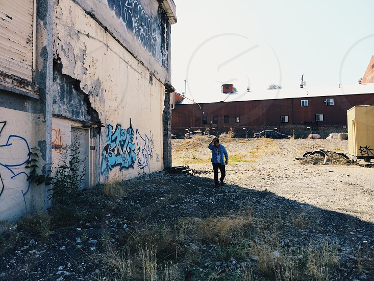 man walking in the shadow of an abandoned building photo