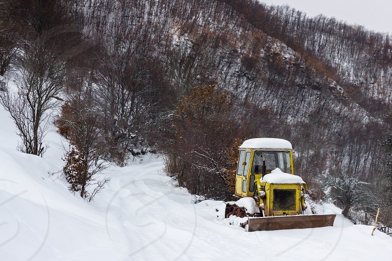 Rusty old yellow bulldozer for snow on a mountain covered by snow and dead orange trees photo