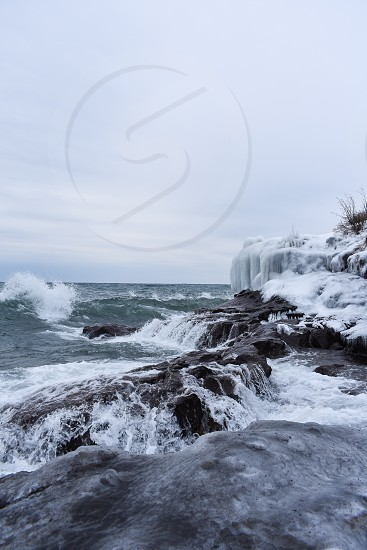 Rugged ice covered shoreline with waves breaking over the rocks photo