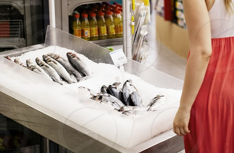 Woman shopping for fish in a supermarket standing looking at a display of fresh whole fish on ice photo