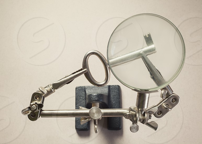 Conceptual composition finding the solution key as symbol magnified with an old tool for soldering.  photo