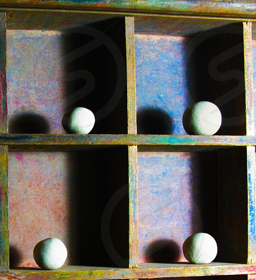 four brown shelves with white ball shaped objects on top photo