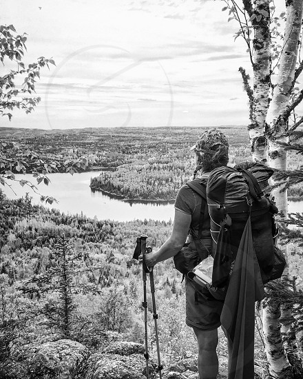 Female backpacker looking out over forest and lake vista black and white photo