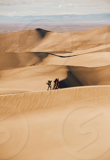 Hikers follow the ridgeline of the sand dunes to find a place to camp photo