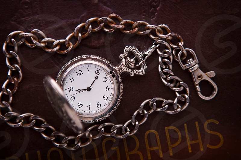 Still life of a vintage stop watch and old photo album photo