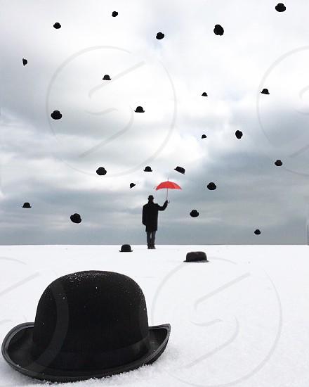 raining black bucket hat and man holding red umbrella photo