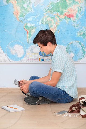 Boy sitting by the map in classroom photo