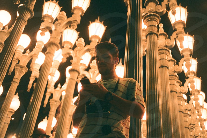 man holding up smartphone below lighted sconce street lamps photo