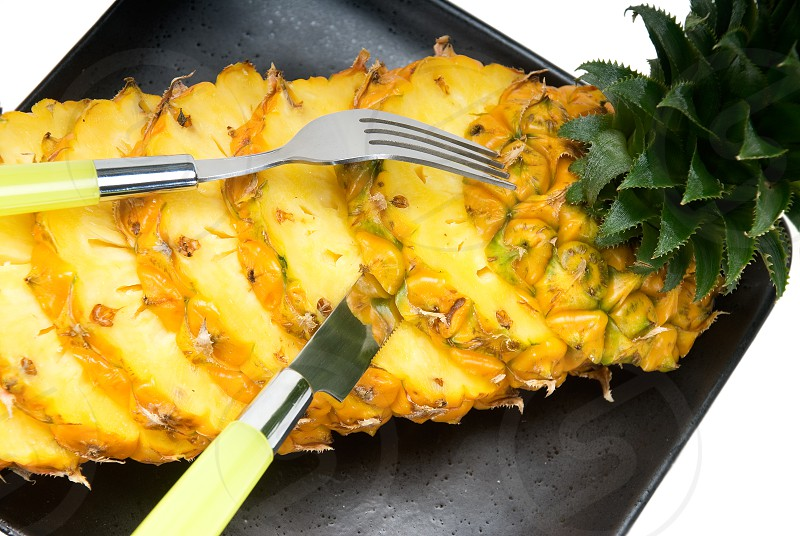 ripe vibrant pineapple sliced on a black plate with knife and fork photo