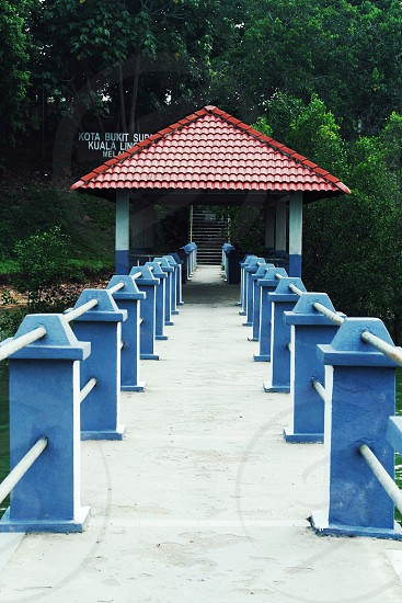 blue and white railings towards black stairs near brown roof photo