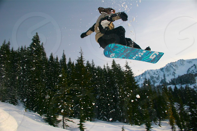 person in tan and black winter gear snowboarding photo