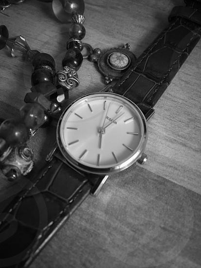 black and white analog watch beside beaded bracelet photo