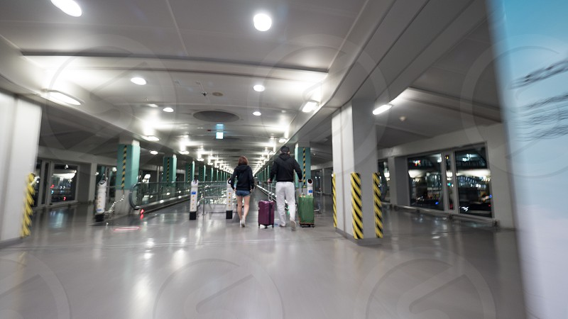 People with luggage walking on the moving walkway at the airport terminal of Seoul South Korea photo