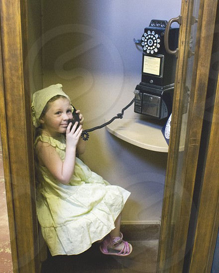 Girl dressed in old country dress with old pay telephone photo