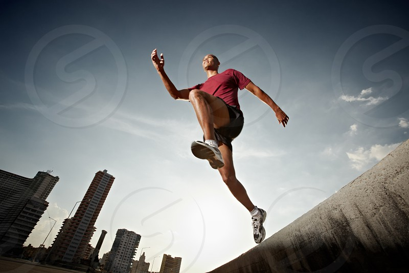Young athlete running and jumping from a wall with urban landscape in background photo