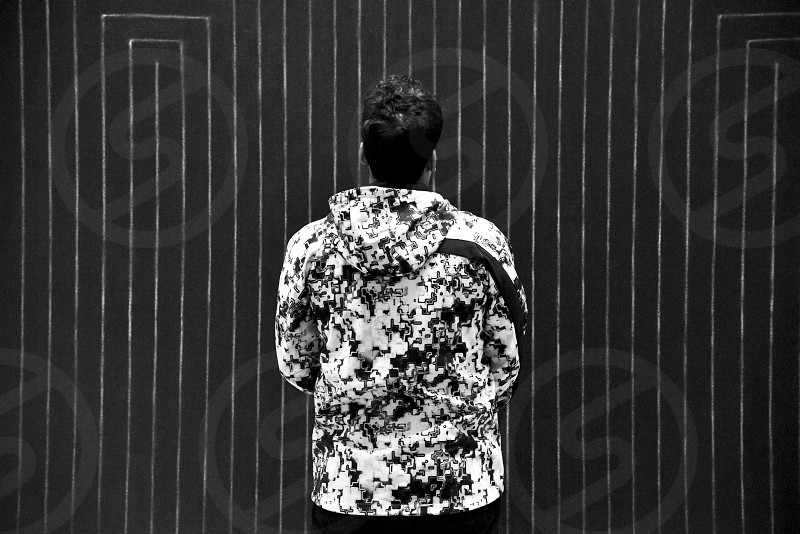 man in camouflage hoodie standing in front of striped wall greyscale photography photo