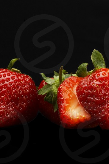 fresh vivid colored strawberry over black background photo