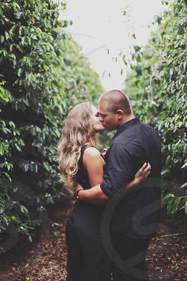 woman wearing black sleeveless blouse kiss man wearing black button down shirt photo