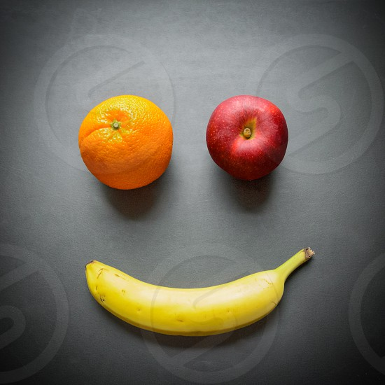 Fruit still life featuring an orange a red apple and a ripe banana forming a smiling happy face. photo