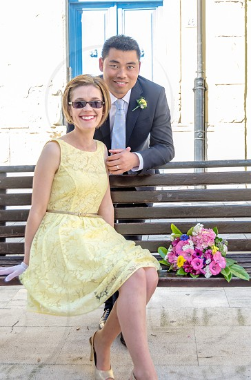 woman wearing a yellow lace dress sitting on a park bench while a man leans over her smiling photo