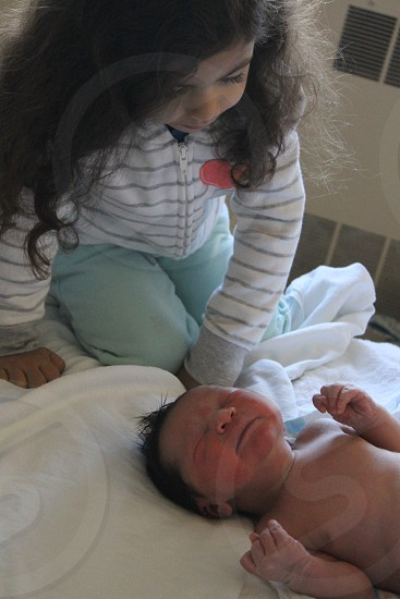 girl and a baby on white textile inside the room photo
