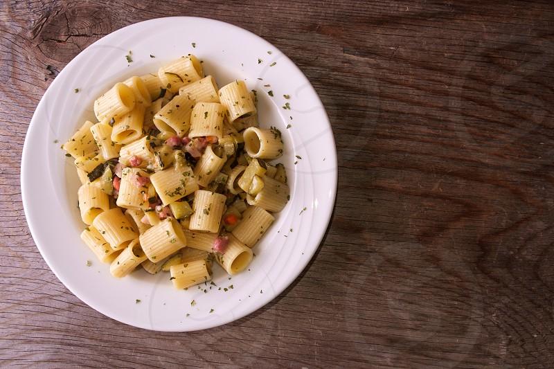 Rigatoni pasta with bacon and zucchini photo