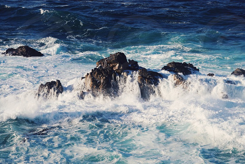 sea waves hitting rocks in sea during daytime photo