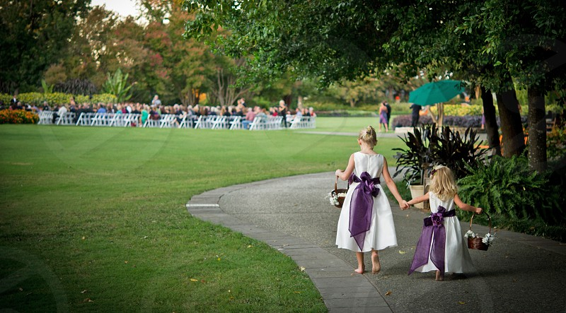 two flower girls heading to the beautiful outdoor wedding photo