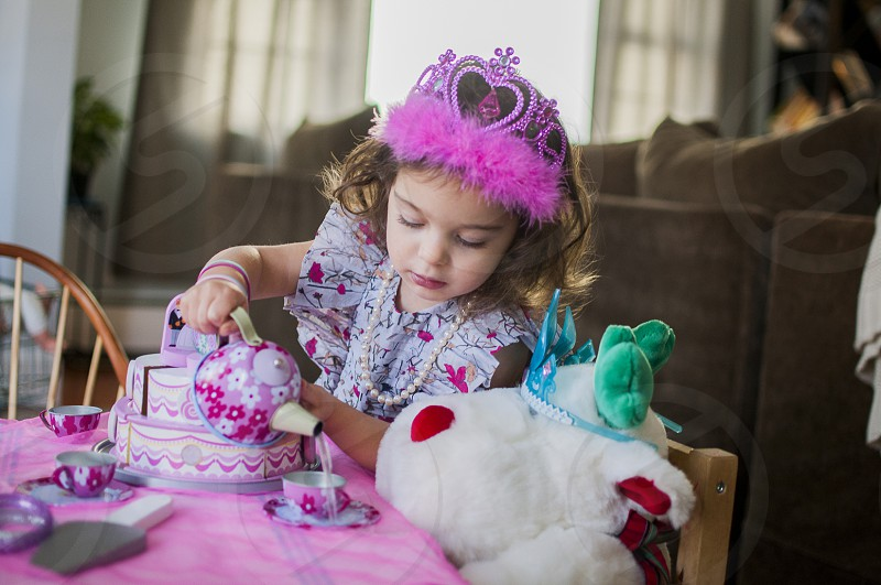girl in purple and pink floral dress and pink crown having tea party with white and red plush bear photo