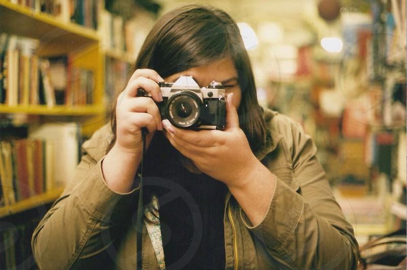 woman taking photo with camera near books photo