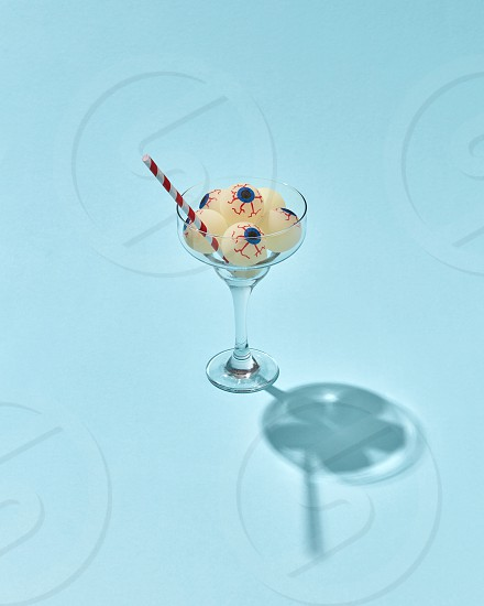 Cocktail glass with big eyeballs and plastic drinking straw as a Halloween treat on a light blue background with shadows copy space. photo