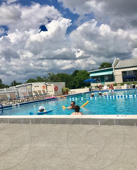 Swimming pool summer cloudy skies swimming activities people fun public pool people  photo