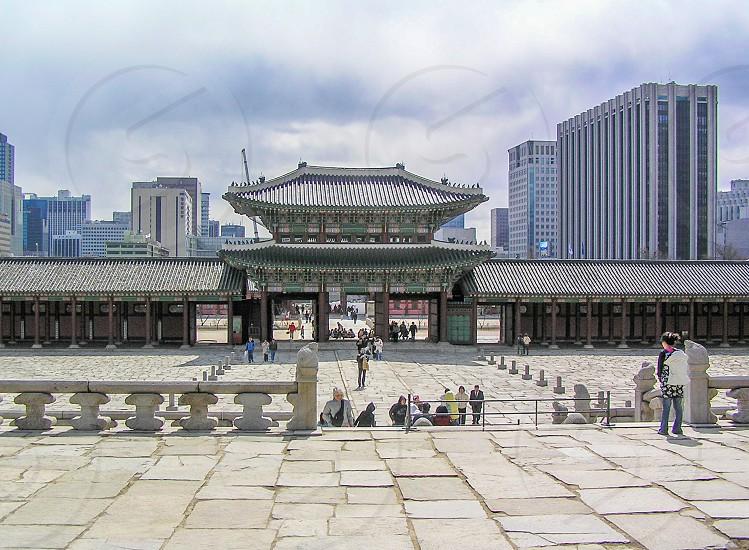 people walking through Asian gate through concrete pavement photo