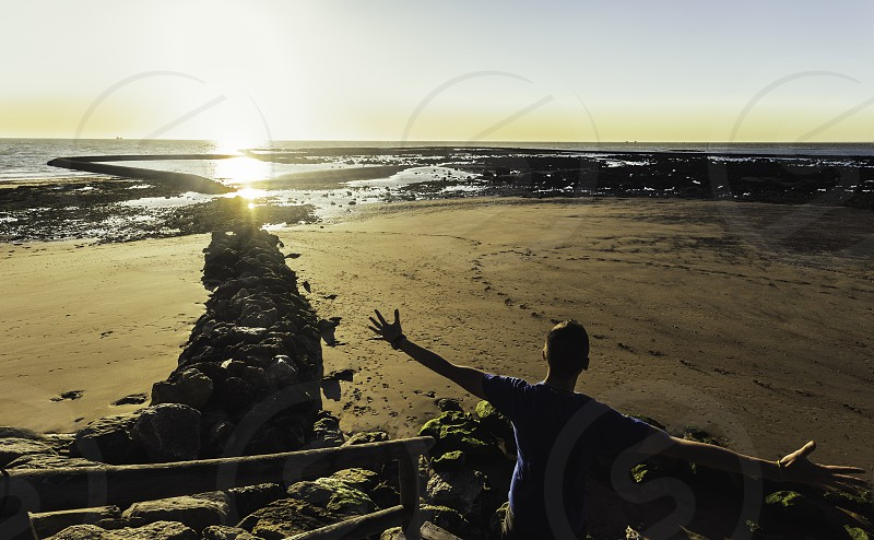 Young man with  arms outstretched looking at sunset on the beach of Sanlucar de Barrameda photo