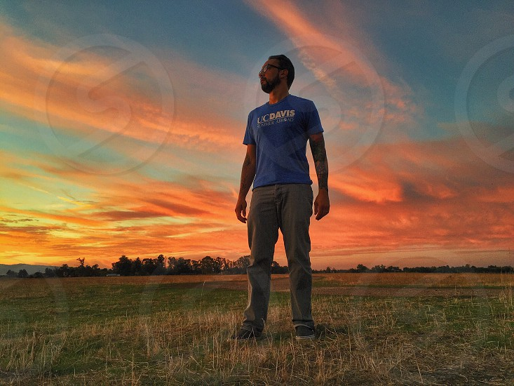 man in blue and white ucdavis crew neck t shirt and grey denim jeans on green and brown grassy field under blue sky during orange sunset photo