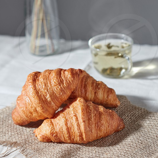 Morning breakfast with homemade tasty freshly baked french bakery on a textile and cup of green tea on a gray textile background copy space. photo