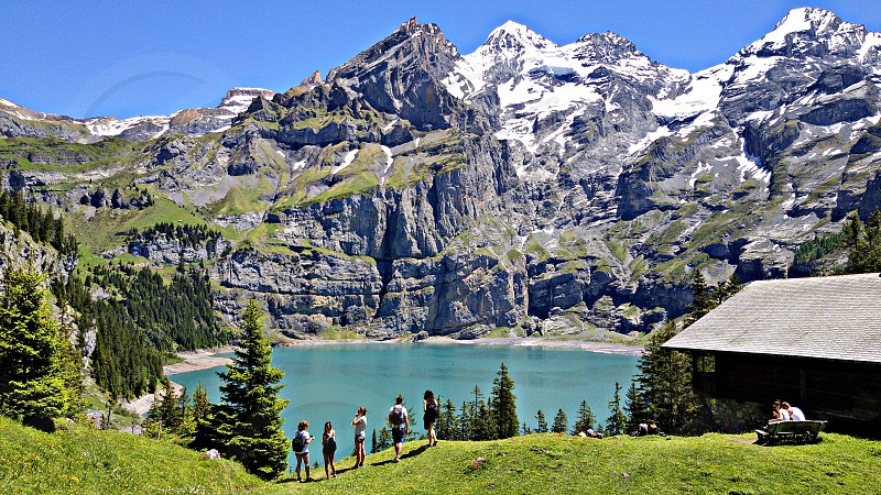 lake beside rock mountain with house and people standing surrounded with pine trees photo